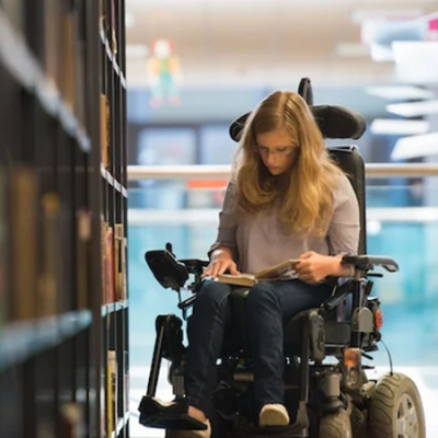 Woman using power wheelchair and reading book at library