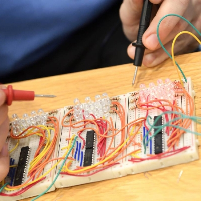 Hands manipulating colorful wires and electronics
