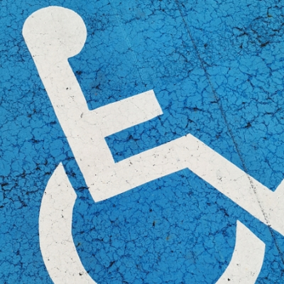 blue and white International Wheelchair Symbol painted on ground