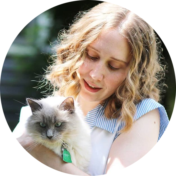 Head shot of Anna Moyer, young white woman with light brown hair, holding cat